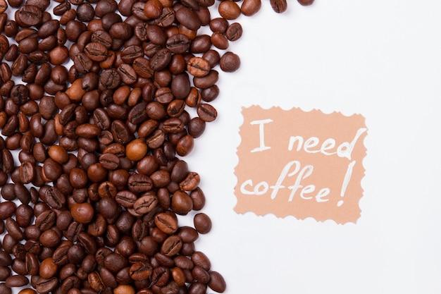 Veel koffiebonen op wit oppervlak en bericht. ik heb koffie nodig.
