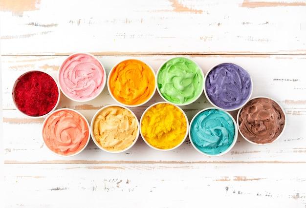 Veel kopjes met kleurrijk regenboog-ijs. bovenaanzicht