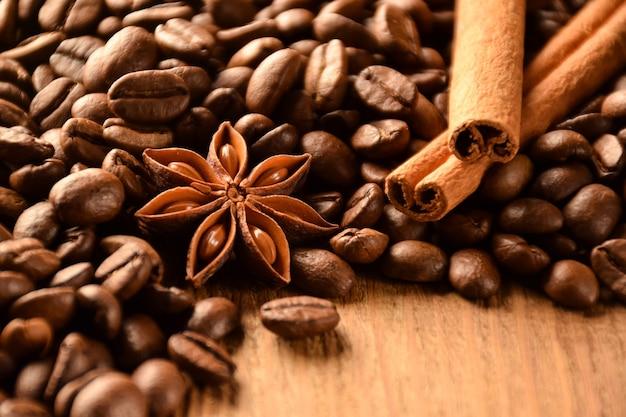 Veel korrels koffie, anijs en kaneel liggen op een bruin houten oppervlak