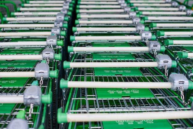 Veel lege groene winkelwagentjes in rij