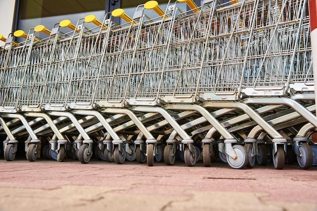 Veel lege winkelwagentjes op de parkeerplaats van de winkel. rij winkelwagens voor supermarktkopers