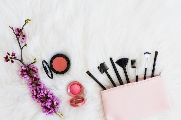 Veel make-up borstels uit roze zak; bloemtakje en compact gezichtspoeder op zachte witte vacht