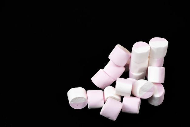Veel marshmallow snoepjes op een zwarte achtergrond. detailopname