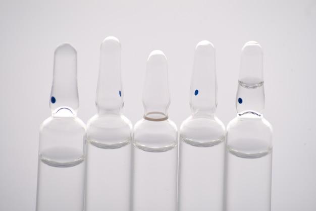 Veel medische ampullen op een rij op een wit oppervlak. detailopname