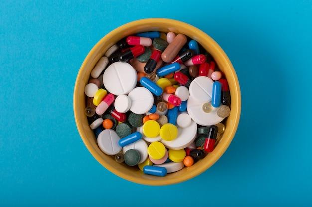 Veel medische pillen en capsules in een kom op een blauwe achtergrond, bovenaanzicht