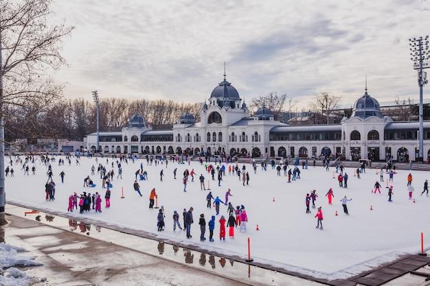 Veel mensen brengen hun vakantie door met schaatsen op de ijsbaan van het stadspark in boedapest, hongarije