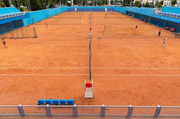 Veel mensen, kinderen tennissen op rode grunt tennisbaan