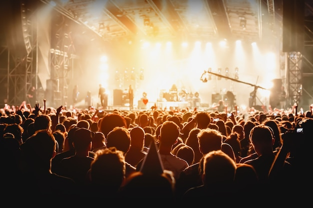 Veel mensen, menigte op concert, oranje licht van podium.
