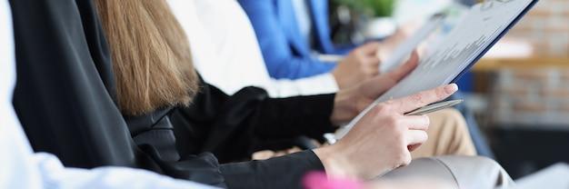 Veel mensen met documenten in hun handen zitten in een bedrijfstrainingsclose-up