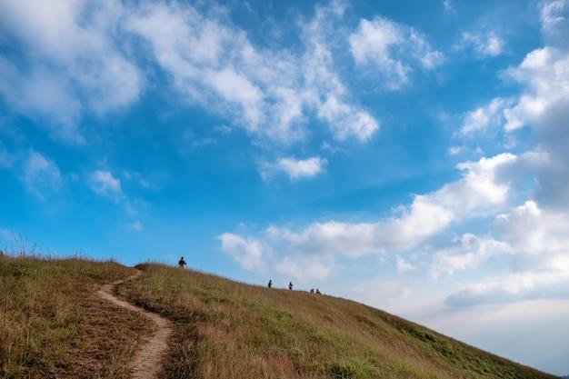 Veel mensen wandelen op een hoge berg met een prachtige natuur, schilderachtige en blauwe hemelachtergrond