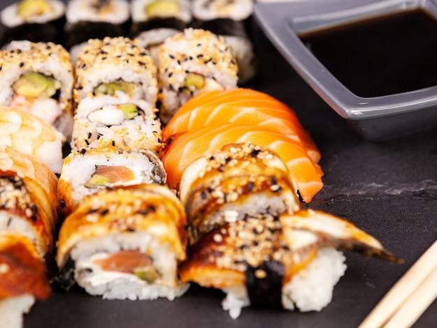 Veel mix van verschillende sushi-broodjes op zwarte stenen achtergrond in studiofoto
