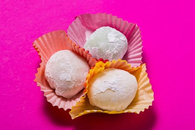 Veel mochi dessert in papieren bekers op roze tafel