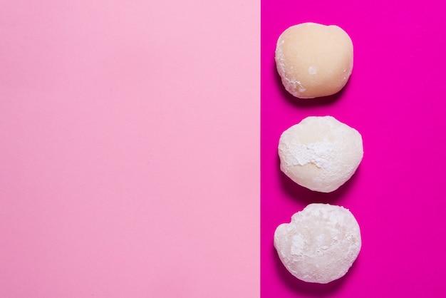 Veel mochi dessert op roze tafel, kopie ruimte