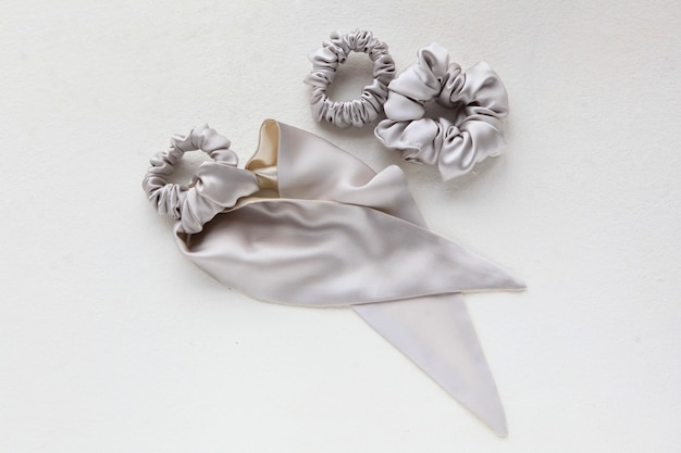 Veel moderne zijde zilver scrunchy voor haar op een witte achtergrond plat lag set
