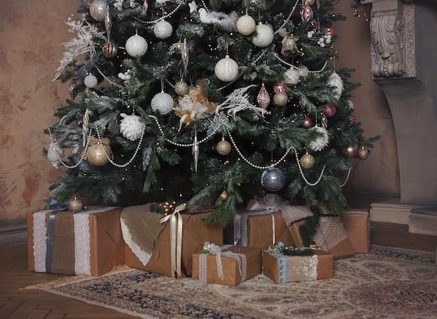 Veel mooie geschenken, in rustieke stijl, liggen onder een versierde kerstboom