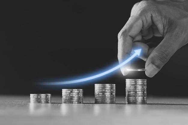 Veel munten zijn op elkaar gestapeld en er zijn digitale grafieken over financiële groei.