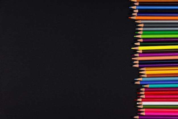 Veel nieuwe kleurrijke potloden op een zwarte achtergrond
