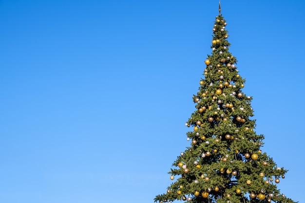 Veel nieuwjaarsversieringen en slingers op een grote kerstboom buiten op een blauwe hemelachtergrond