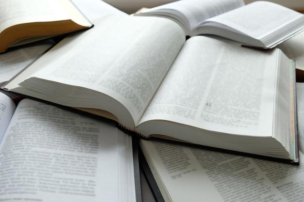 Veel open boeken liggen op tafel onderwijsconcept