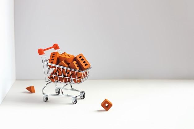Veel oranje bakstenen in de winkelwagen. concept op constructie of zelfisolatie.