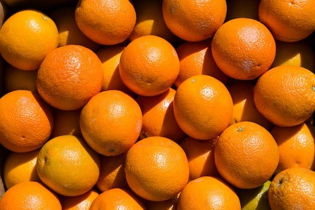 Veel oranje fruit op een markt tijdens zonnige dag.