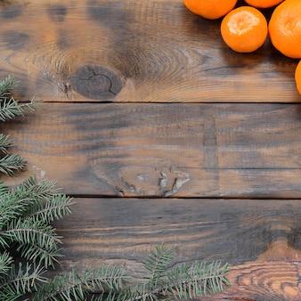 Veel oranje mandarijnen en takken van de kerstmisspar liggen op bruine houten planken