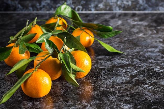 Veel oranje mandarijnen met groene bladeren op een donkere ondergrond. kopieer ruimte.