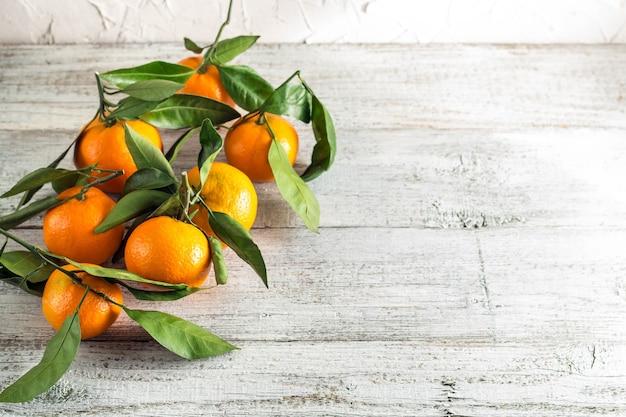 Veel oranje mandarijnen met groene bladeren op witte houten achtergrond. ruimte kopiëren.