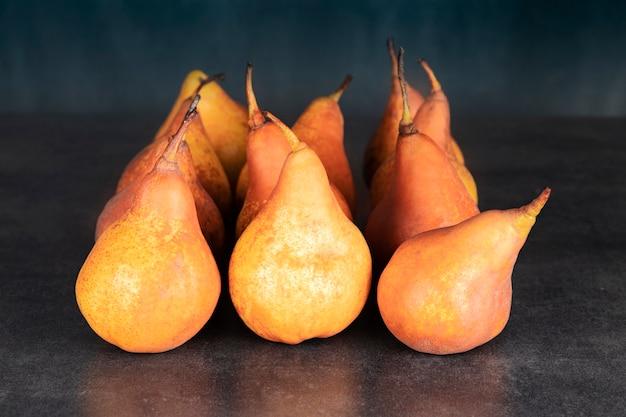Veel oranje peren uit de herfstoogst op een donkere stenen tafel