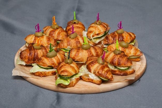 Veel overheerlijke mini sandwich croissants op een rond houten bord.