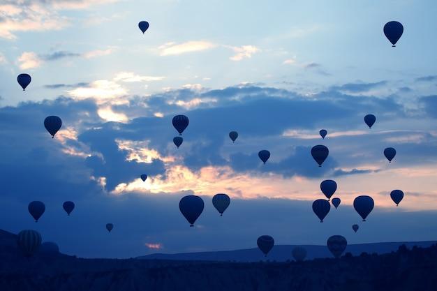 Veel passagiersballonnen vliegen tegen de achtergrond van de dageraad in de wolken