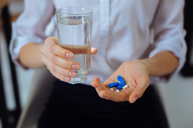 Veel pillen. jonge vrouw die een wit overhemd draagt en glas met water in de rechterhand houdt terwijl hij u gaat helpen
