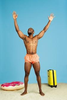 Veel plezier. gelukkige jonge mens die met strandring als doughnut en zak op blauwe ruimte rust
