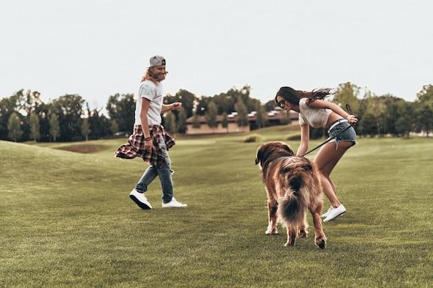 Veel plezier hebben. volledige lengte van een mooi jong stel dat met hun hond speelt terwijl ze buiten zijn