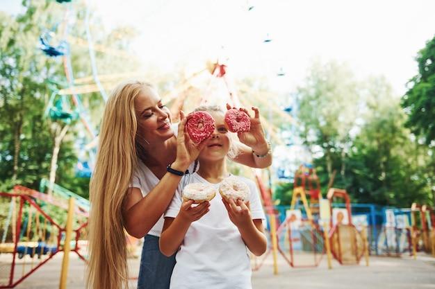 Veel plezier met donuts. vrolijk meisje haar moeder heeft een goede tijd samen in het park in de buurt van attracties.