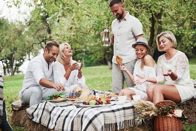Veel plezier met lachen. groep volwassen vrienden hebben een rust en een gesprek in de achtertuin van het restaurant tijdens het diner