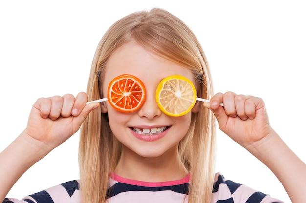 Veel plezier met snoepjes. vrolijk meisje dat ogen bedekt met lolly's en glimlacht terwijl ze op wit wordt geïsoleerd