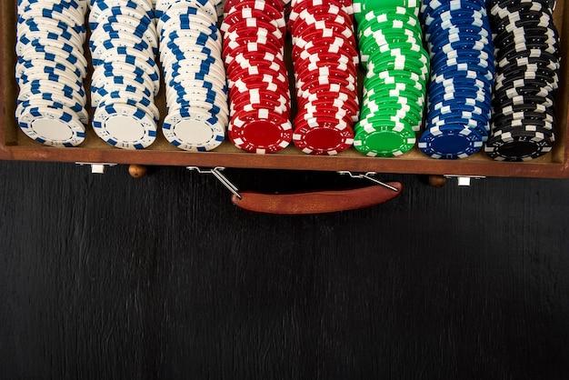 Veel pokerfiches in een koffer geïsoleerd op een zwart oppervlak