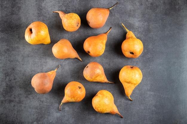 Veel rijpe gele peren op een grijze stenen tafel