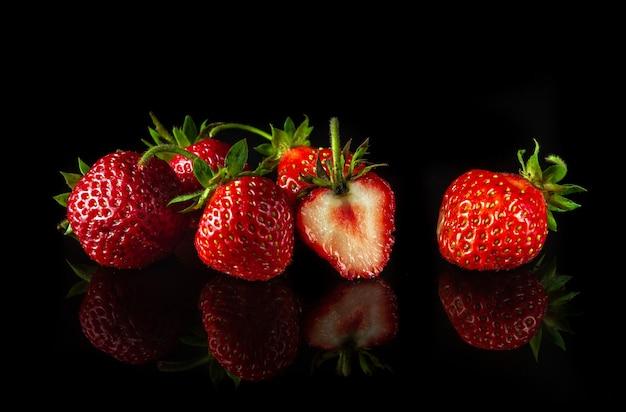 Veel rijpe rode aardbeien op een zwarte achtergrond