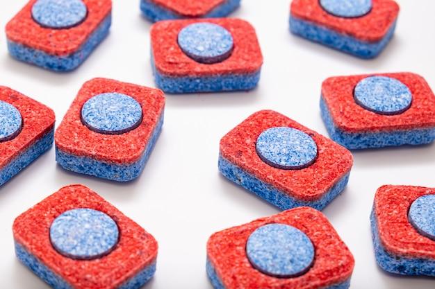 Veel rode en blauwe vaatwastabletten op witte achtergrond, keukenapparatuur en oplossingen voor het afwassen