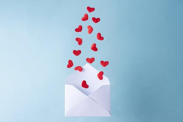 Veel rode harten vliegen uit een witte envelop, valentijnsdag, close-up.