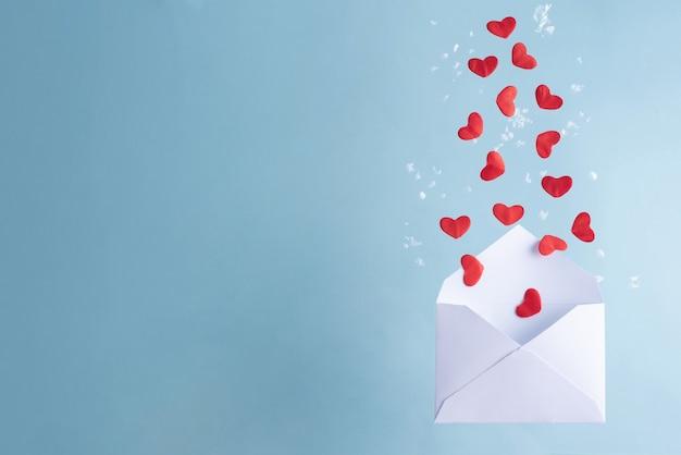 Veel rode harten vliegen uit een witte envelop, valentijnsdag.