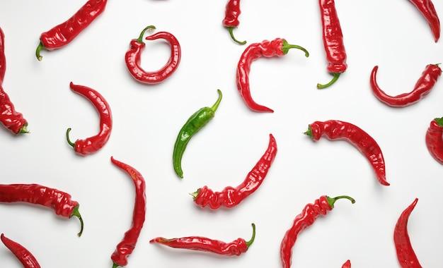 Veel rode hele vruchten van hete peper en één groene
