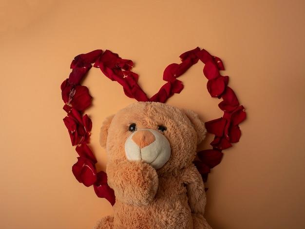 Veel rode rozenblaadjes liggen in de vorm van een groot rood hart en in het midden van dit hart ligt