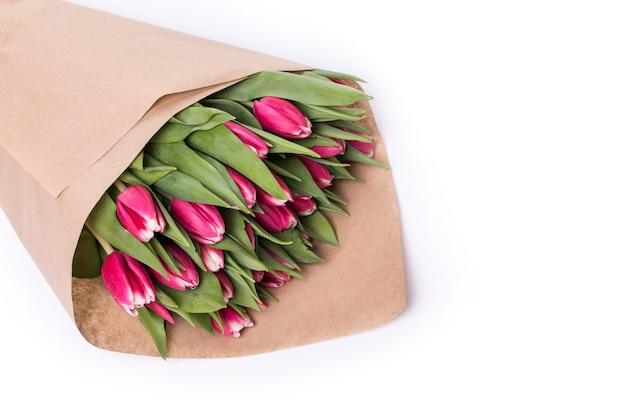 Veel rode tulpen in bruin papier geïsoleerd op wit