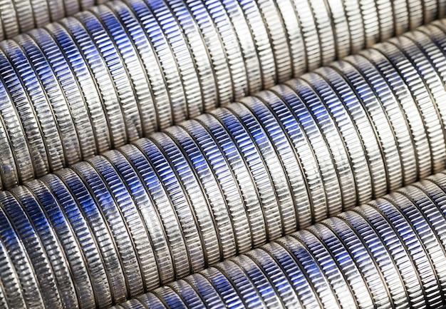 Veel ronde metalen munten van zilverkleurig blauw verlicht