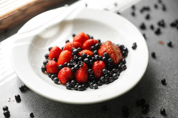 Veel sappige verse rijpe rode aardbeien en bramen liggen in een witte keramische plaat op tafel onder fel zonlicht