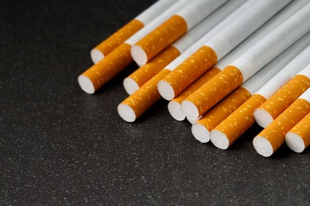 Veel sigaretten worden op een zwarte achtergrond geplaatst, ze zijn schadelijk voor de gezondheid.