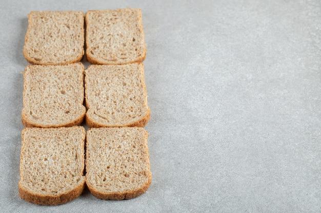 Veel sneetjes bruin brood op een grijze achtergrond.
